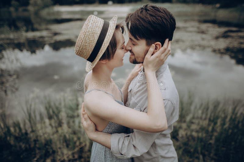 Stilvolle Hippie-Paare, die am See küssen Mann- und Frauenumfassung, lizenzfreie stockbilder