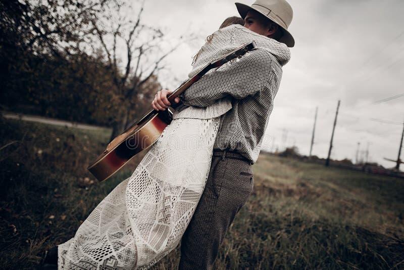 Stilvolle Hippie-Paare umarmen auf dem Gebiet, hübsche Cowboymusiker wi stockfoto