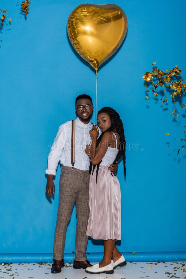 stilvolle junge Afroamerikanerpaare, die mit geformtem Ballon des goldenen Herzens aufwerfen stockfoto