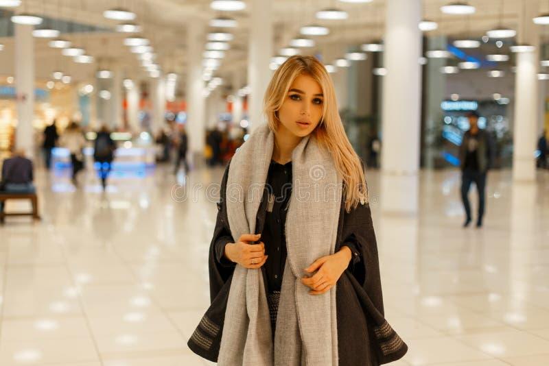 Stilvolle junge Blondine in einem luxuriösen modischen Herbstweinlesemantel mit einem modernen warmen Schal gehen stockfotografie