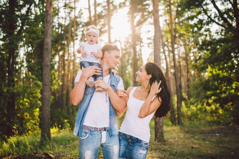 Stilvolle junge Familie der Mutter, des Vatis und der Tochter eine j?hrige Blondine, die nahe Vater auf Schultern, drau?en au?erh lizenzfreie stockfotos