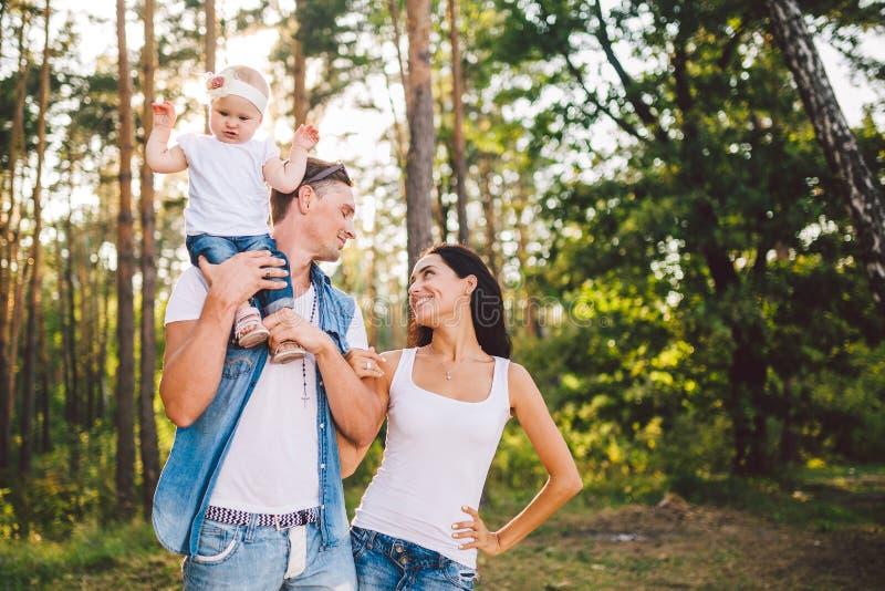 Stilvolle junge Familie der Mutter, des Vatis und der Tochter eine j?hrige Blondine, die nahe Vater auf Schultern, drau?en au?erh lizenzfreies stockfoto