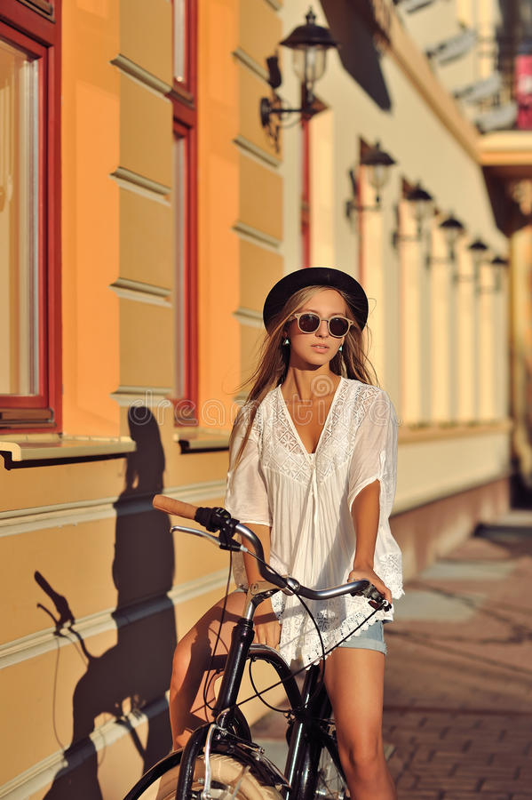 Stilvolle junge Frau auf einem Retro- Fahrrad Im Freienart und weiseportrait stockbilder
