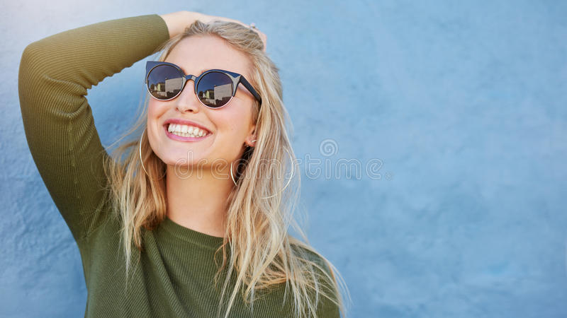 Stilvolle junge Frau beim Sonnenbrillelächeln lizenzfreie stockfotografie