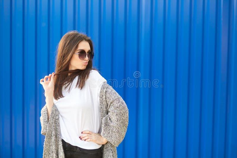Stilvolle junge Frau in der Sonnenbrille lächelnd gegen blauen Hintergrund stockbild