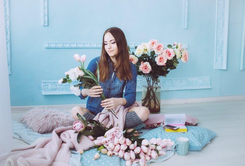 Stilvolle junge Frau, die auf dem Boden, Blumenblumenstrauß von den rosa Tulpen im hellen sonnenbeschienen Raum mit blauen Wänden lizenzfreies stockbild