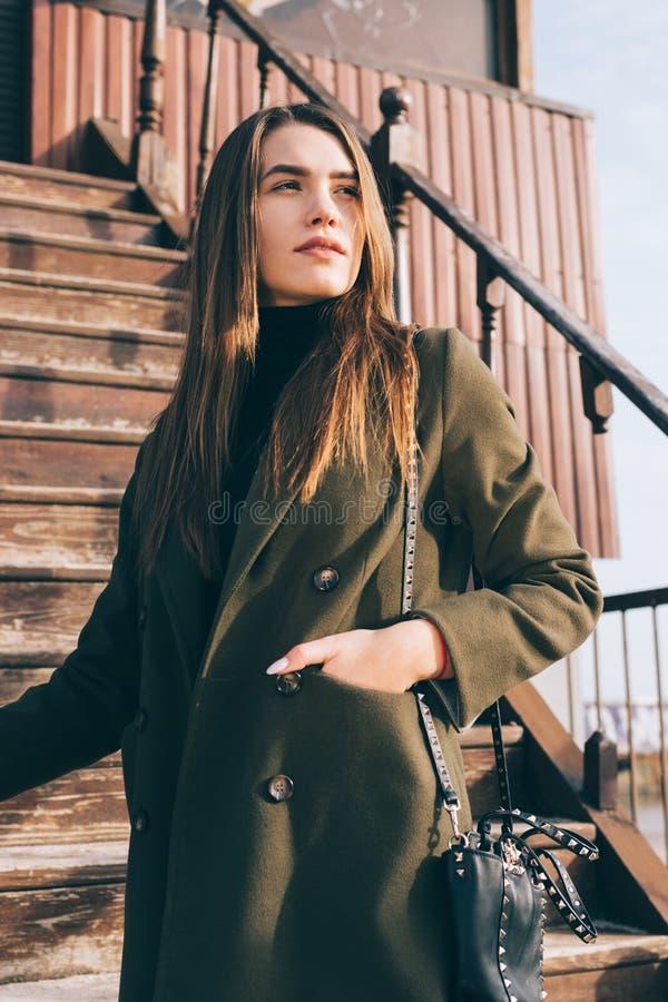 Stilvolle junge Frau, die auf einem alten hölzernen Treppenhaus aufwerfend steht stockfotos