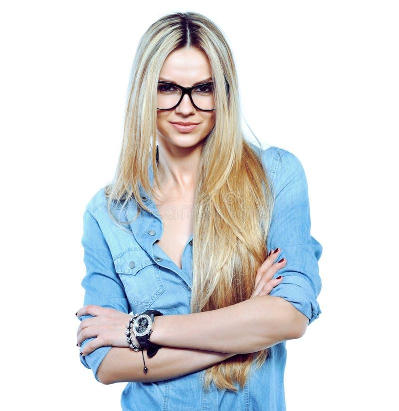 Stilvolle junge Frau, die in den tragenden Gläsern des Studios an lokalisiert aufwirft stockfoto