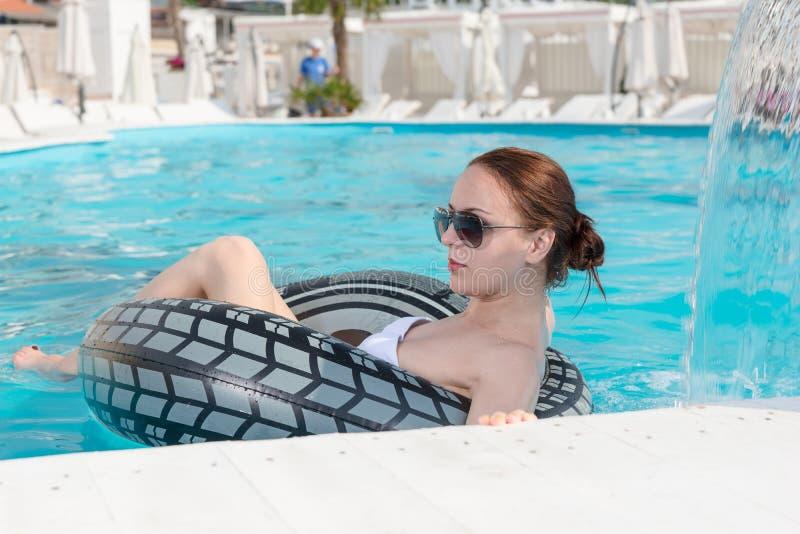 Stilvolle junge Frau, die in einem Swimmingpool sich entspannt lizenzfreie stockbilder
