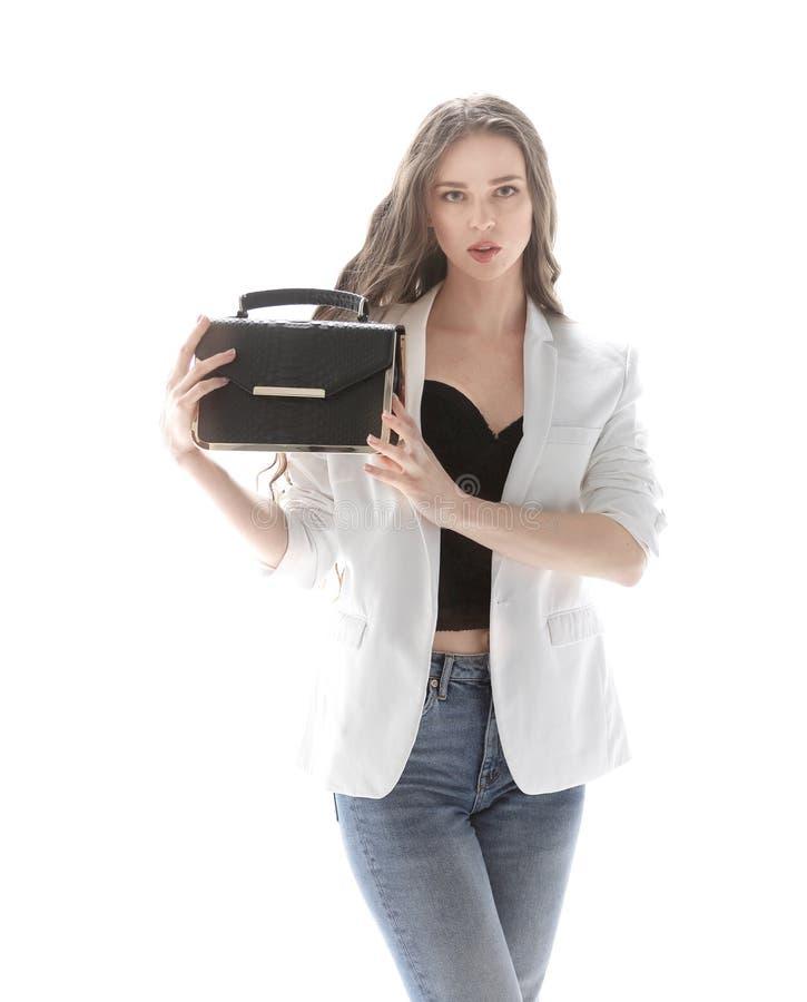 Stilvolle junge Frau, die ihre moderne Handtasche zeigt Lokalisiert auf Weiß lizenzfreie stockfotografie