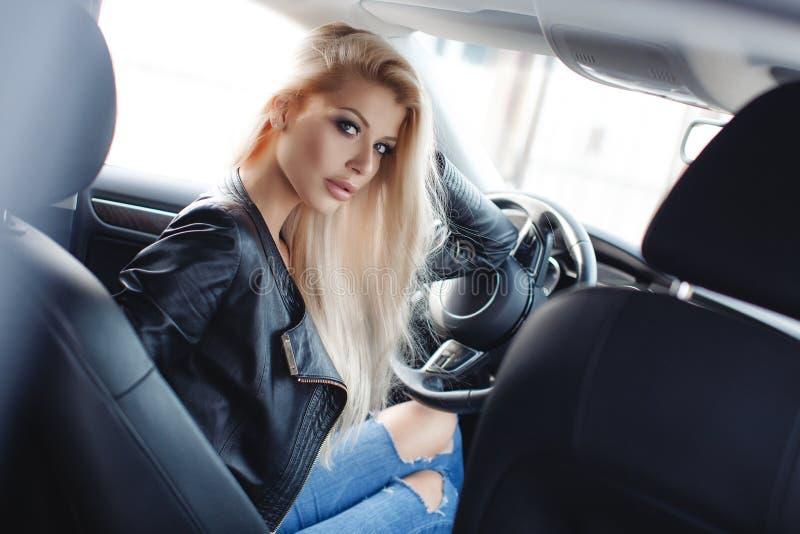 Stilvolle junge Frau mit dem langen blonden Haar, das auf dem Fahrer ` s Sitz eines prestigevollen Autos sitzt stockfoto