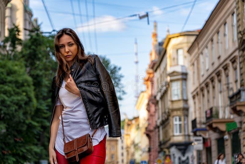 Stilvolle junge Frau steht auf der Straße von Lemberg Straßenmodefotografie mit schönem Mädchen stockfotografie