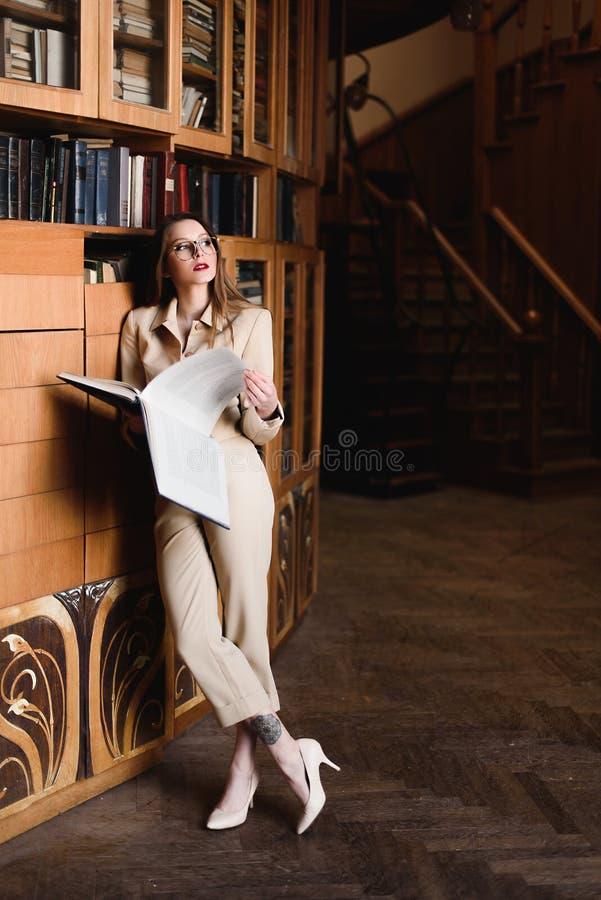 Stilvolle junge Geschäftsdame in den Gläsern liest ein Buch an der Bibliothek lizenzfreies stockbild