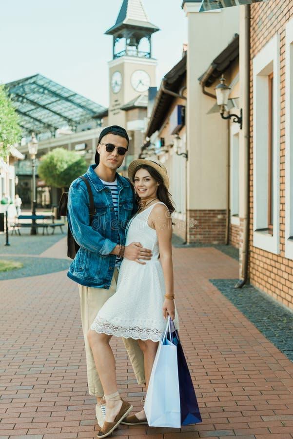 Stilvolle junge Paare, die Einkaufstaschen halten und an der Kamera lächeln stockfotografie