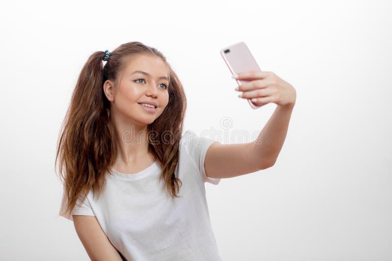 Stilvolle lächelnde junge Frau, die selfie mit ihrem intelligenten Telefon nimmt stockfoto