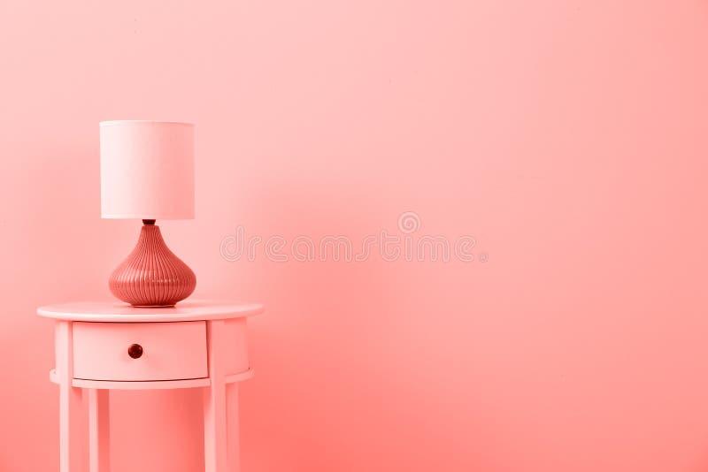 Stilvolle Lampe auf Tabelle gegen Farbwand, Raum für Text stockbilder