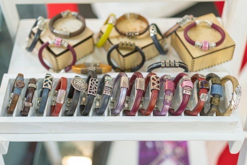 Stilvolle Lederarmbänder im Geschäft Viel verschiedene Leder- und Textilarmbänder Lederne mehrfarbige Armbänder im Geschäft stockfotos