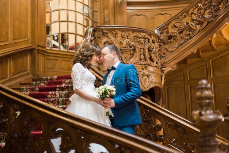 Stilvolle Luxusbraut und hübscher eleganter Bräutigam, die vertrauliches Händchenhalten mit Blumenstrauß auf alter hölzerner Trep stockfotografie