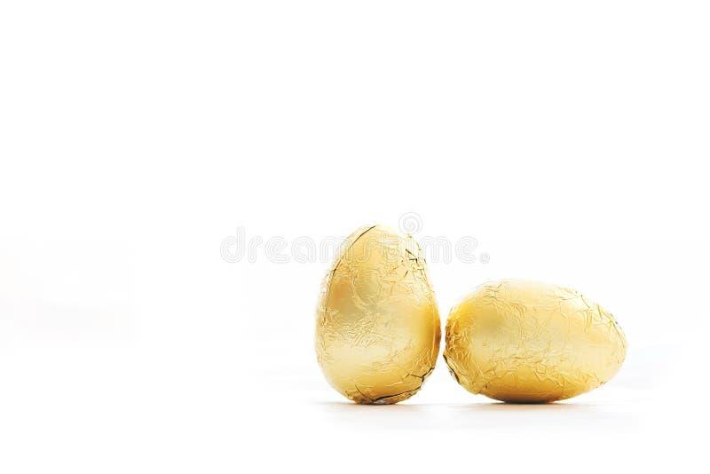 Stilvolle Ostereier in der goldenen Folie lokalisiert auf weißem hellem Hintergrund mit Raum für Text Moderne Schokoladengold-Ost lizenzfreies stockbild