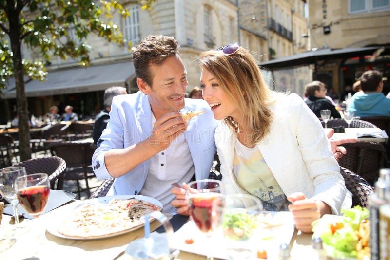 Stilvolle Paare, die das Mittagessen im fantastischen Restaurant essen lizenzfreie stockfotos