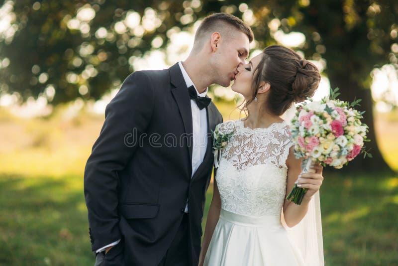 Stilvolle Paare von den glücklichen Jungvermählten, die auf dem Gebiet an ihrem Hochzeitstag mit Blumenstrauß gehen Mitten in dem lizenzfreies stockbild
