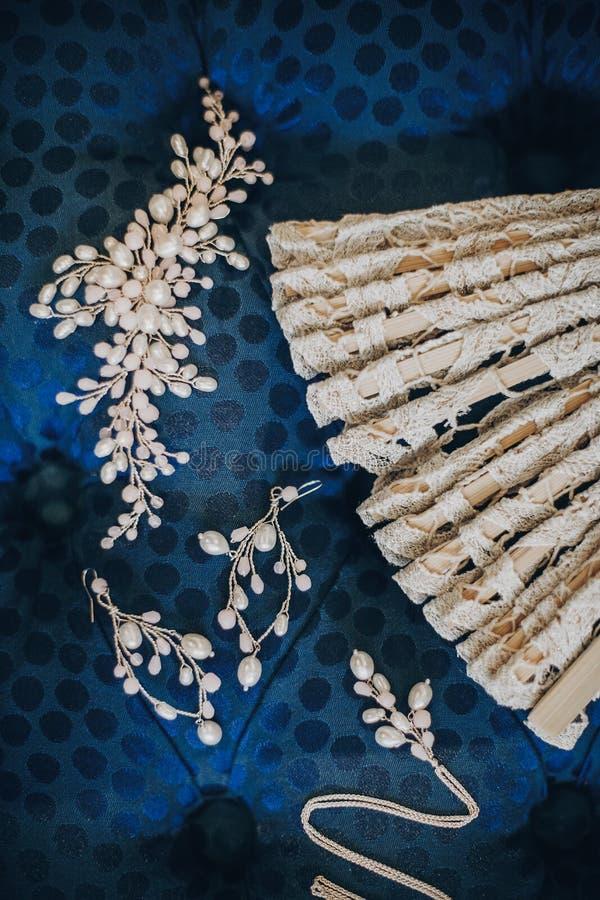 Stilvolle Perlenohrringe, Halskette, Haarnadel und Weinlesefan auf blauem Puff im Hotelzimmer Brautzusätze während des Hochzeitst stockbilder