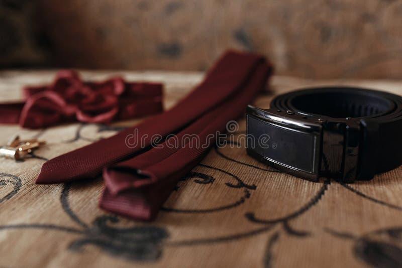 Stilvolle rote Fliege und Bindung mit Gurt und Manschettenknöpfe auf Bett morgen lizenzfreie stockbilder