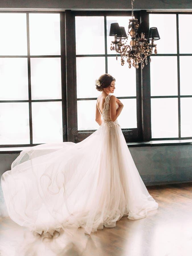 Stilvolle, schöne Braut in einem luxuriösen Kleid, das gegen den Hintergrund eines reichen Innenraums aufwirft Hochzeit der schön stockfotografie