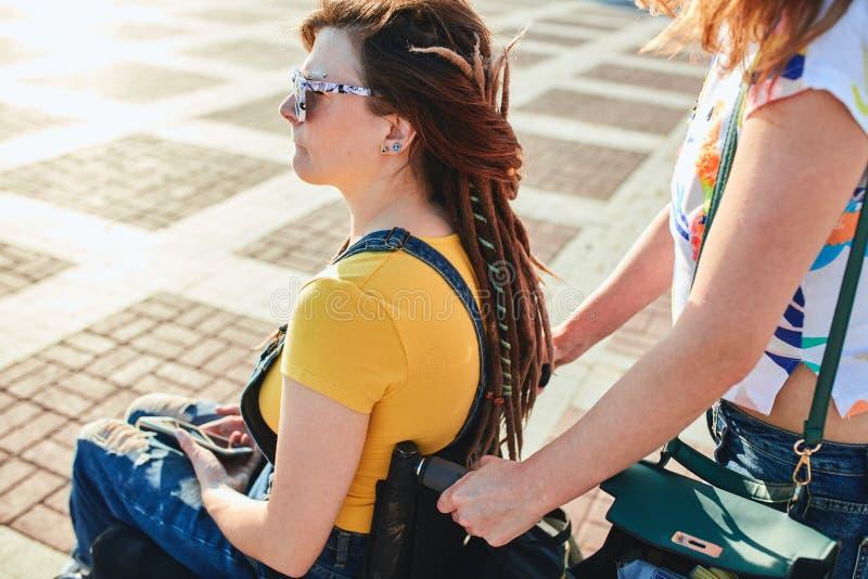 Stilvolle schöne Frau in der Sonnenbrille, die auf dem Rollstuhl sitzt stockbilder