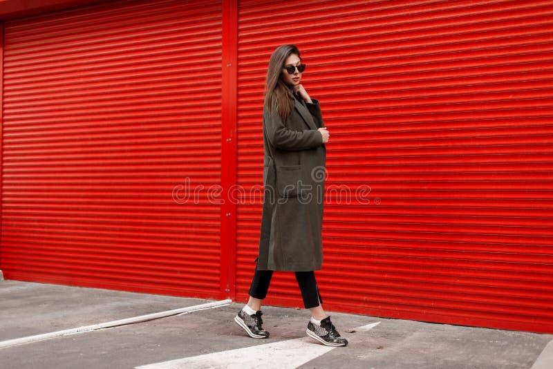 Stilvolle schöne junge attraktive Frau mit Sonnenbrille in einem modernen grünen Mantel auf einem roten Hintergrund gehend auf di stockfoto