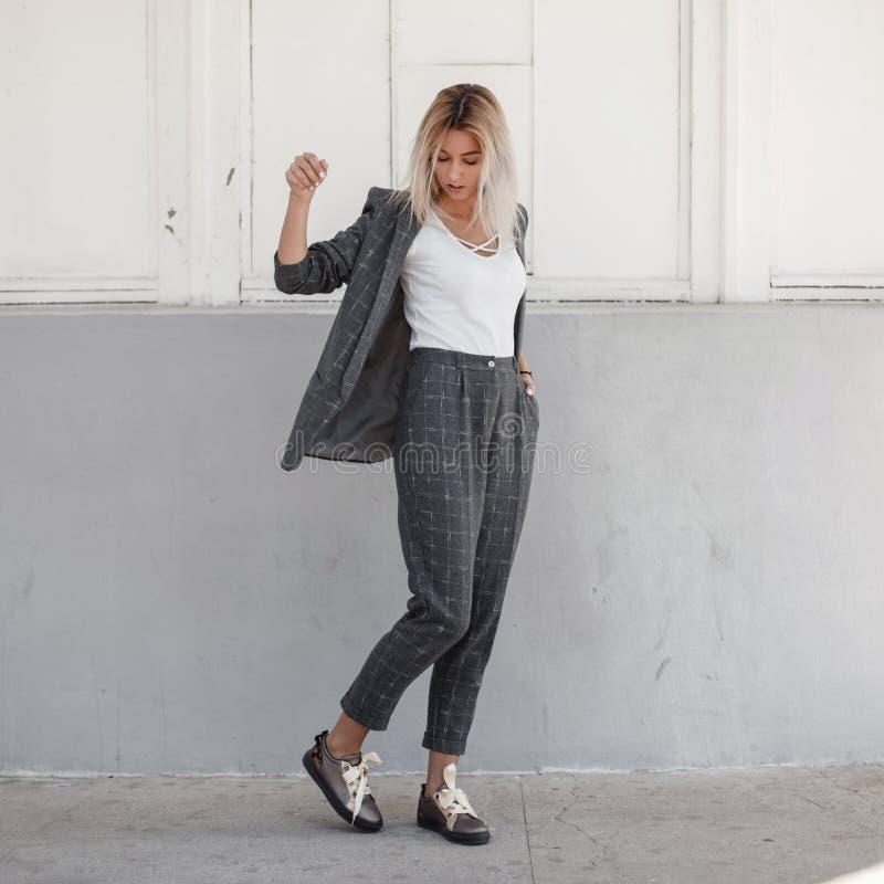 Stilvolle schöne junge Frau in einer grauen Jacke mit lizenzfreie stockbilder