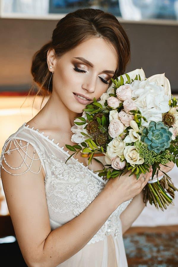 Stilvolle und sinnliche junge braunhaarige vorbildliche Frau mit Hochzeitsfrisur und hellem Make-up, im stilvollen Spitzekleid mi stockfoto