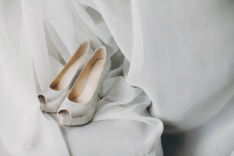 Stilvolle weiße Schuhe für Braut auf weißem Tulle im weichen Morgenlicht im Hotelzimmer Morgenvorbereitung vor Heiratszeremonie stockfotografie