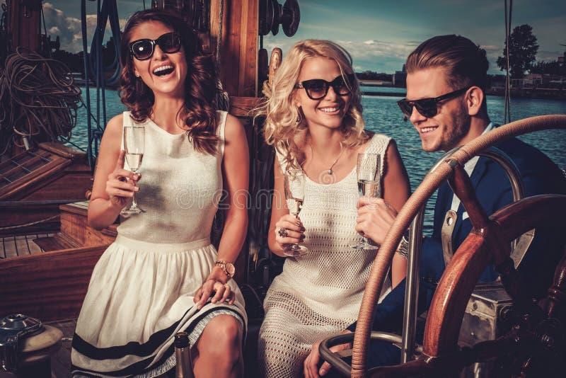 Stilvolle wohlhabende Freunde, die Spaß auf einer Luxusyacht haben lizenzfreie stockbilder