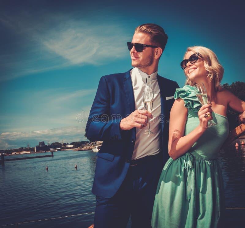 Stilvolle wohlhabende Paare auf einer Yacht stockfotos