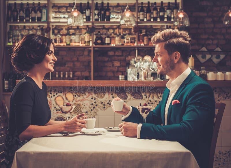 Stilvolle wohlhabende Paare, die Wüste und Kaffee zusammen trinken lizenzfreie stockfotografie