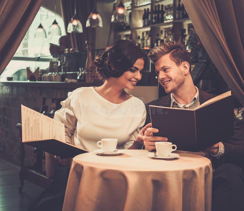 Stilvolle wohlhabende Paare mit Menü lizenzfreie stockbilder