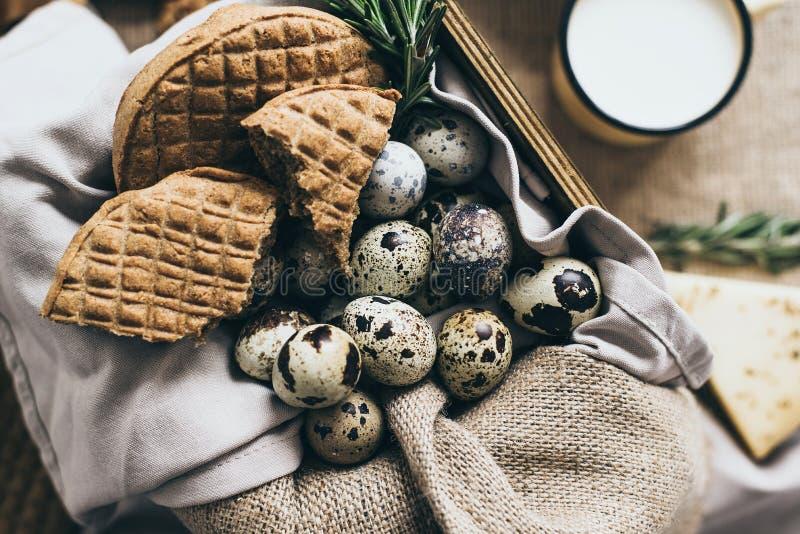 Stilvolle Zusammensetzung des biologischen Lebensmittels bereitete sich für Frühstück Eier, Käse vor Brot und Kräuter in einem Te lizenzfreie stockfotos
