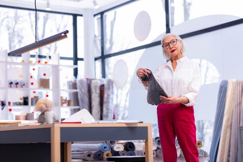 Stilvoller älterer Chef-Designer, der Gewebeproben im Büro aussortiert stockbilder