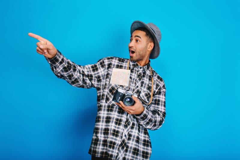 Stilvoller überraschter hübscher Kerl des Porträts mit Kamera, Karte, im Hut, der Spaß auf blauem Hintergrund hat Reisen, genieße lizenzfreie stockbilder