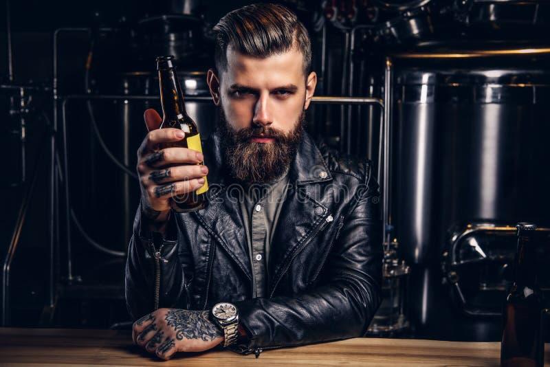 Stilvoller bärtiger Radfahrer kleidete die schwarze Lederjacke, die am Stangenzähler in der indie Brauerei sitzt stockfotos