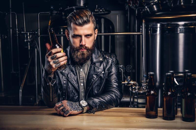 Stilvoller bärtiger Radfahrer kleidete die schwarze Lederjacke, die am Stangenzähler in der indie Brauerei sitzt lizenzfreie stockbilder