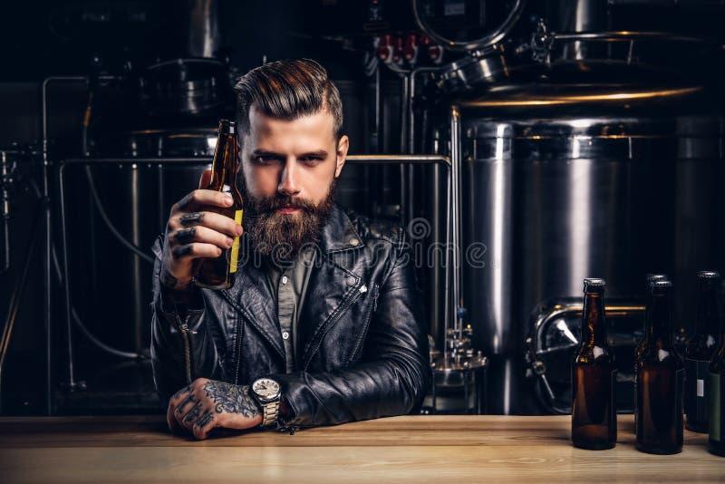 Stilvoller bärtiger Radfahrer kleidete die schwarze Lederjacke, die am Stangenzähler in der indie Brauerei sitzt lizenzfreies stockfoto