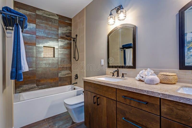 Stilvoller Badezimmerinnenraum mit doppeltem Eitelkeitskabinett stockbild
