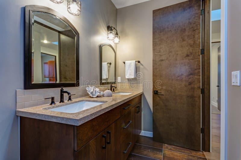 Stilvoller Badezimmerinnenraum mit doppeltem Eitelkeitskabinett stockbilder