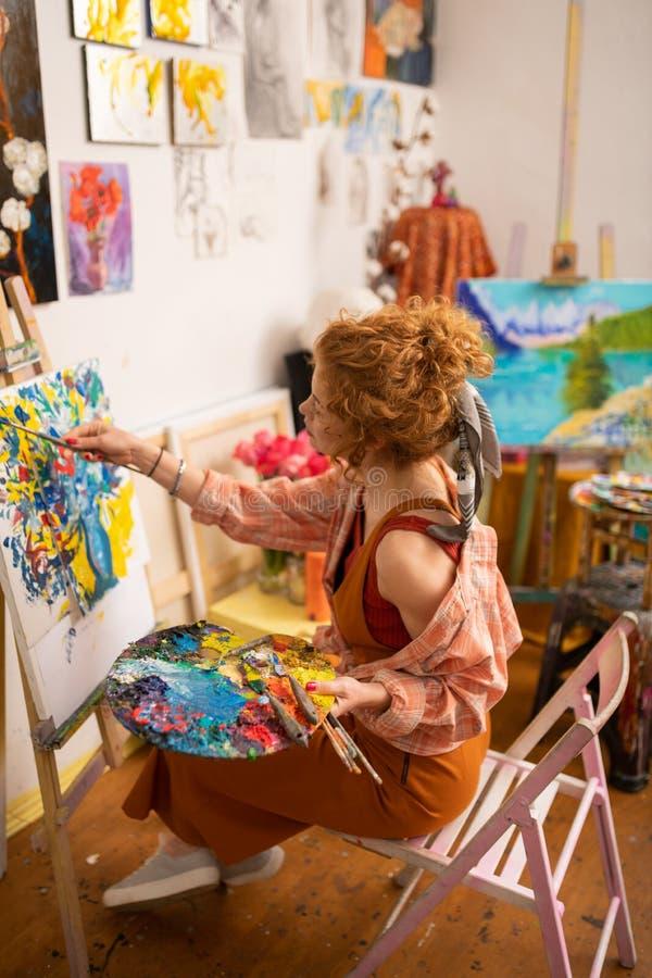 Stilvoller begabter Künstler, der beim Malen auf Segeltuch erstaunlich sich fühlt lizenzfreies stockbild