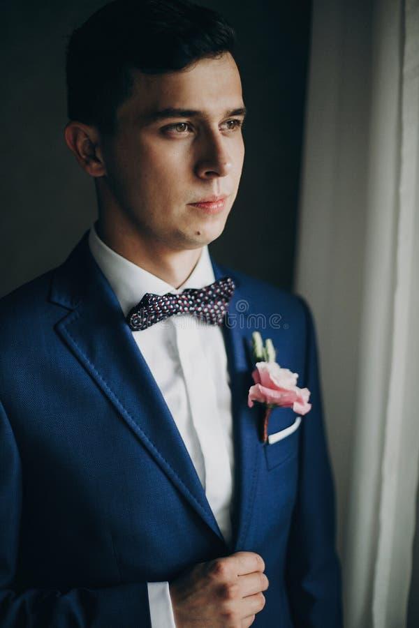 Stilvoller Bräutigam im blauen Anzug, mit Fliege und Boutonniere mit der rosa Rose, die nahe Fenster im Hotelzimmer aufwirft Morg stockfotos