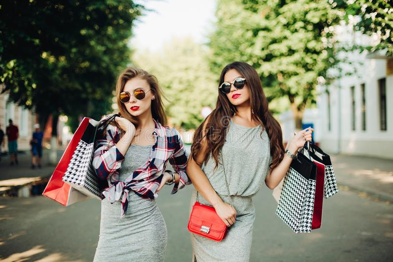 Stilvoller Brunette und Blondine nach dem Einkaufsc$gehen am Park stockfotografie