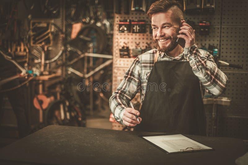 Stilvoller Fahrradmechaniker nimmt Bestellung telefonisch in seiner Werkstatt entgegen lizenzfreies stockbild