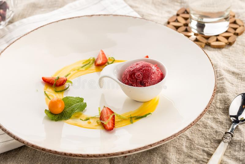 Stilvoller feinschmeckerischer Nachtisch mit dem Erdbeereis und Frucht gedient auf weißer Platte am Restaurant lizenzfreie stockbilder
